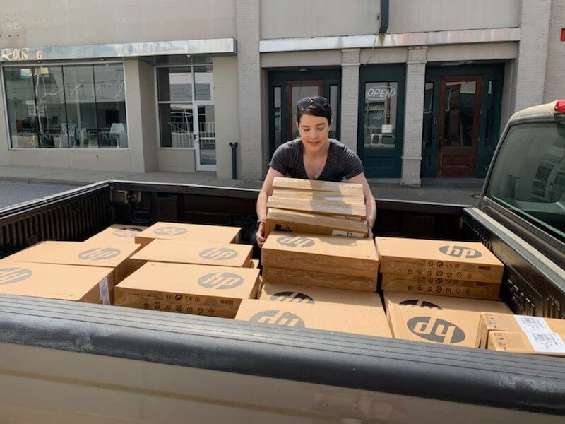 This photo shows The Enterprise Center staff member Mary Smith unloading boxes of laptops from the back of a pickup truck.