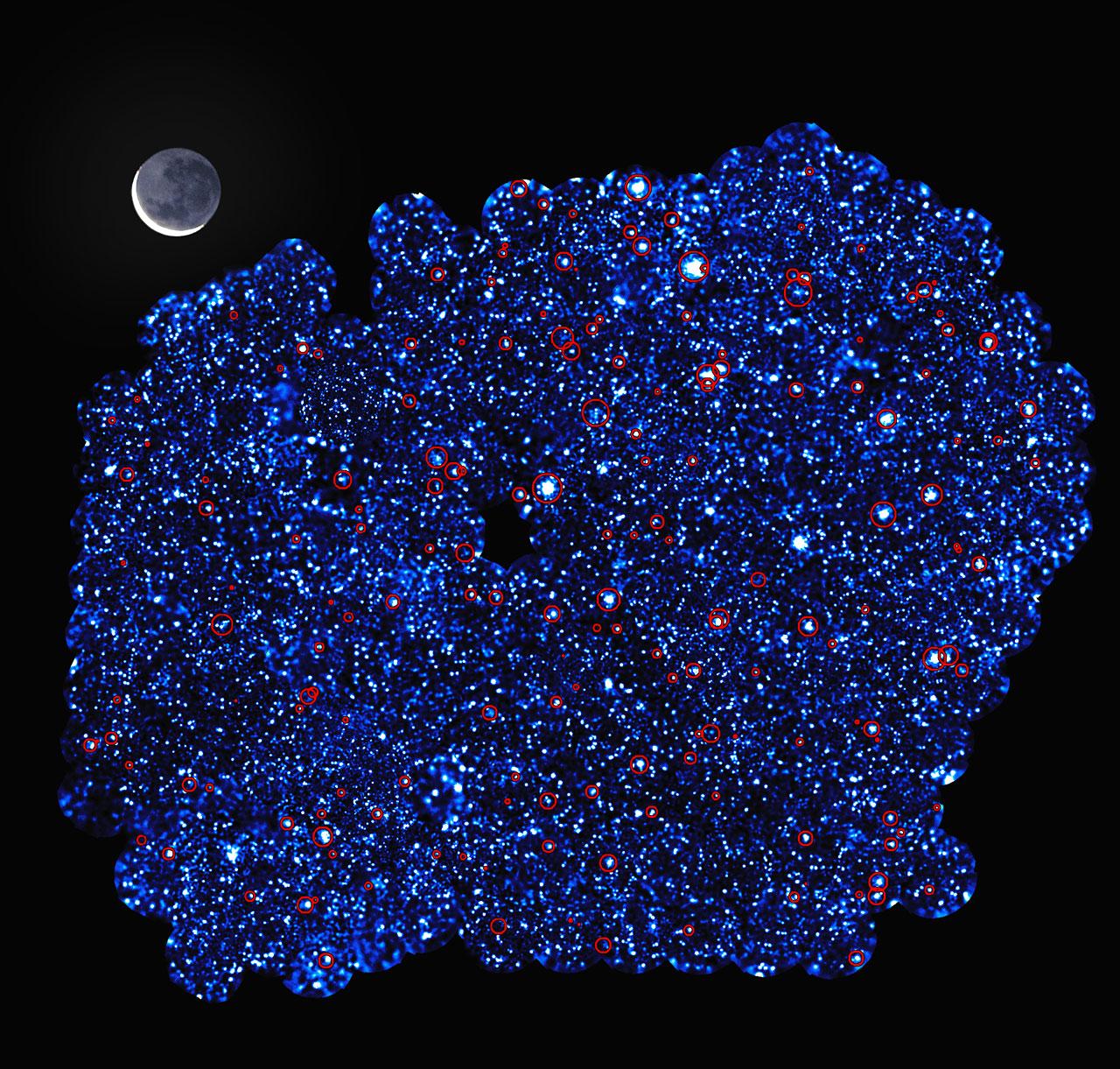 Esta imagen muestra el área sur XXL (o XXL-S, por sus siglas en inglés), uno de los campos observados por el sondeo XXL. El sondeo XXL es una de las mayores búsquedas jamás emprendidas de cúmulos de galaxias y proporciona, por lejos, la mejor vista del cielo profundo de rayos X que se haya logrado hasta la fecha. Los círculos rojos de esta imagen muestran los cúmulos de galaxias detectados en el sondeo.  En conjunto con el otro campo – el área norte XXL (o XXL-N, por sus siglas en inglés) – se descubrieron cerca de 450 de estos cúmulos en el sondeo, que los trazó hacia una época del pasado en que el Universo tenía la mitad de su edad actual. La imagen también revela alrededor de 12000 galaxias que tenían núcleos muy brillantes, conteniendo agujeros negros súper masivos que se detectaron en el área. Crédito: ESA/XMM-Newton/XXL survey consortium/(S. Snowden, L. Faccioli, F. Pacaud)
