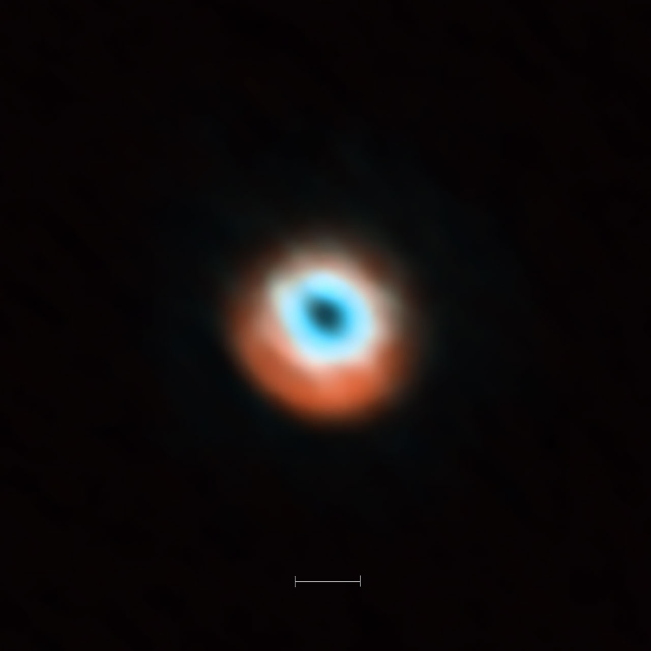 This ALMA image combines a view of the dust around the young star HD 135344B (orange) with a view of the gaseous material (blue). The smaller hole in the inner gas is a telltale sign of the presence of a young planet clearing the disc.