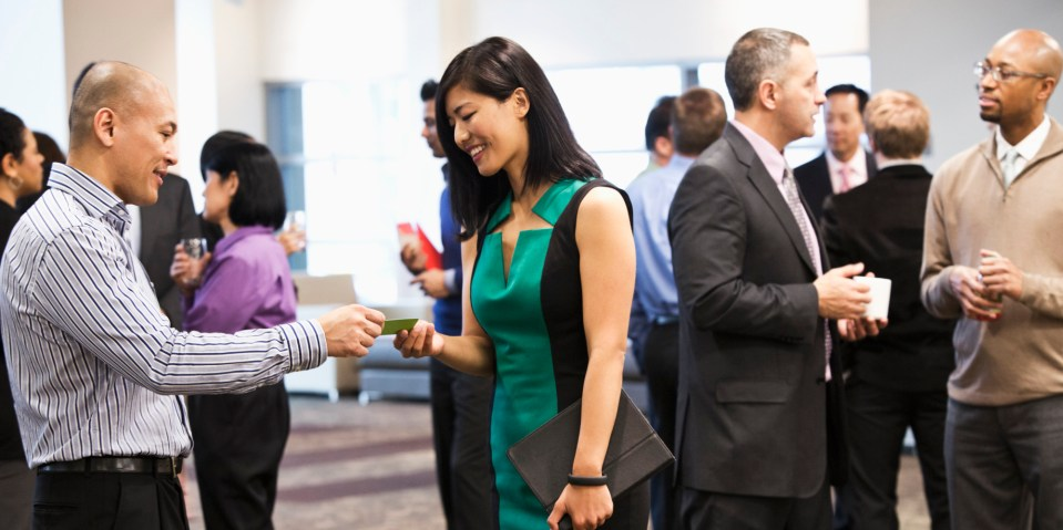 A man and woman exchanging business cards at a crowded networking opportunity at an event like our Learn EB-5 Seminar.