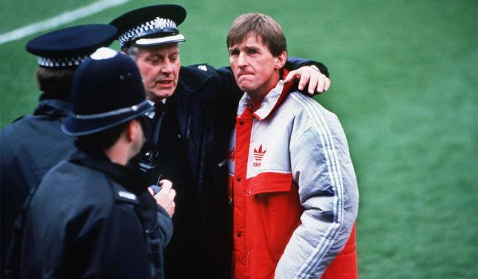 Police console Liverpool manager Kenny Dalglish.