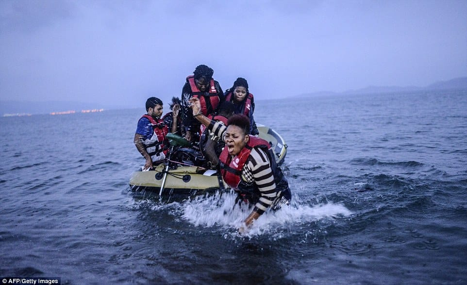 New arrivals: An African migrant topples into the cold water after losing her footing whilst standing in the small rubber dinghy