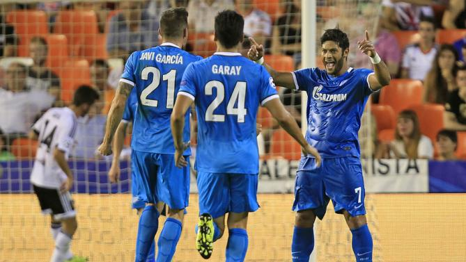 Zenit's Hulk, right, celebrates with teammates Ezequiel Garay, center, and Javi Garcia, left, after scoring against Valencia during a Group H Champions League soccer match between Valencia and Zenit Saint Petersburg, at the Mestalla stadium in Valencia, Spain, Wednesday, Sept. 16, 2015. (AP Photo/Alberto Saiz)