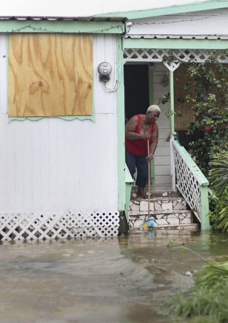 Жительница острова Антигуа выметает из дома воду после прохождения урагана Ирма Центральная Америка, ирма, катастрофа, разрушения, стихийное бедствие, стихия, ураган, флорида