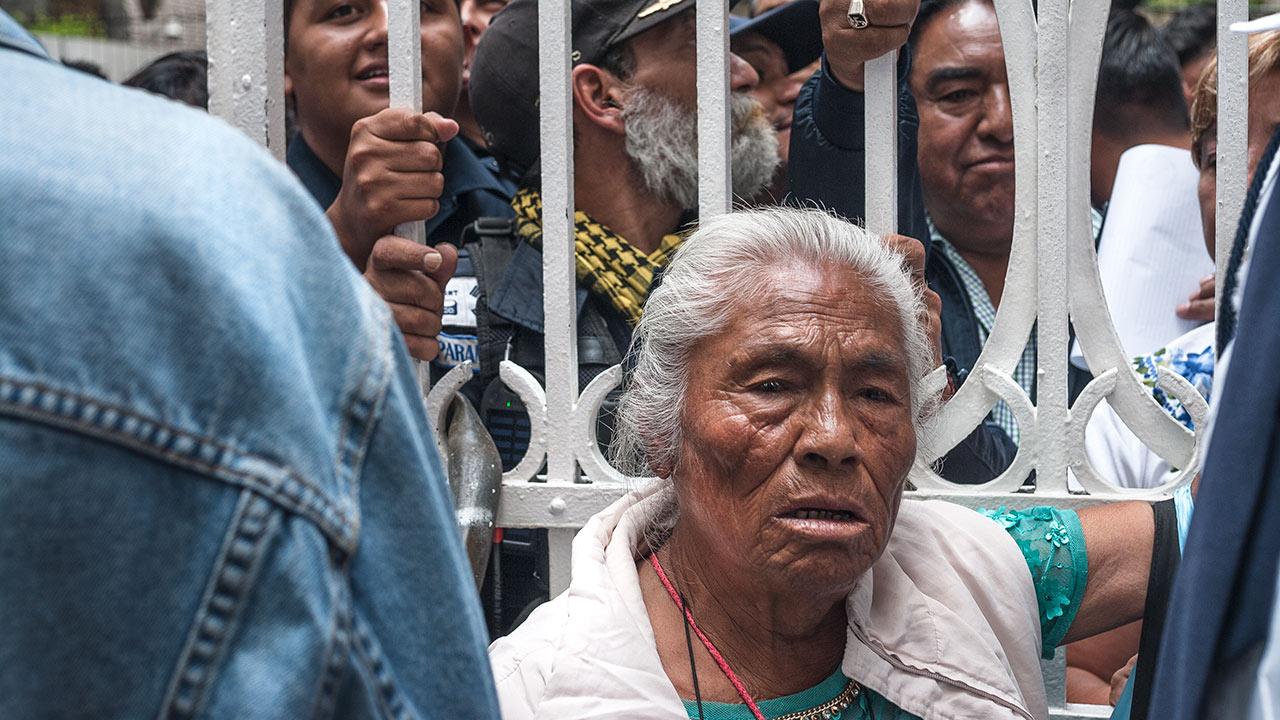 """Una señora, que desde afuera pedía le regresaran su casa, pregunta """"¿qué harán con los adultos mayores que se están muriendo de hambre?"""". Logra ingresar pero no le es permitido el paso más allá de la reja. Foto: Angélica Escobar/Forbes México."""