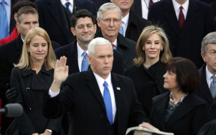 WASHINGTON, DC - JANUARY 20: U.S. Vice President Mike Pence (L) takes the oath of office as his wife Karen Pence looks on, on the West Front of the U.S. Capitol on January 20, 2017 in Washington, DC. In today's inauguration ceremony Donald J. Trump becomes the 45th president of the United States.   Chip Somodevilla/Getty Images/AFP