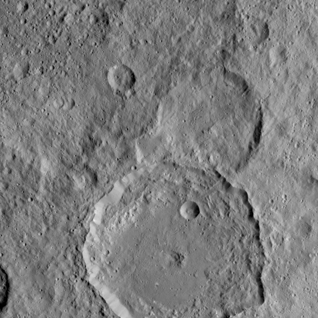 NASA's Dawn spacecraft took this Aug. 18 image of Gaue Crater, the large crater on the bottom. Gaue is a Germanic goddess to whom offerings are made in harvesting rye. The center of this crater is sunken in. Its diameter is 52 mi