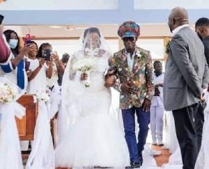 Kojo Antwi walking his fan Efia Antwiwaa Kajah to the altar