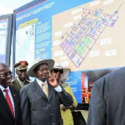 Tanzanian President John Magufuli and Ugandan President Yoweri Museveni stand in front the project