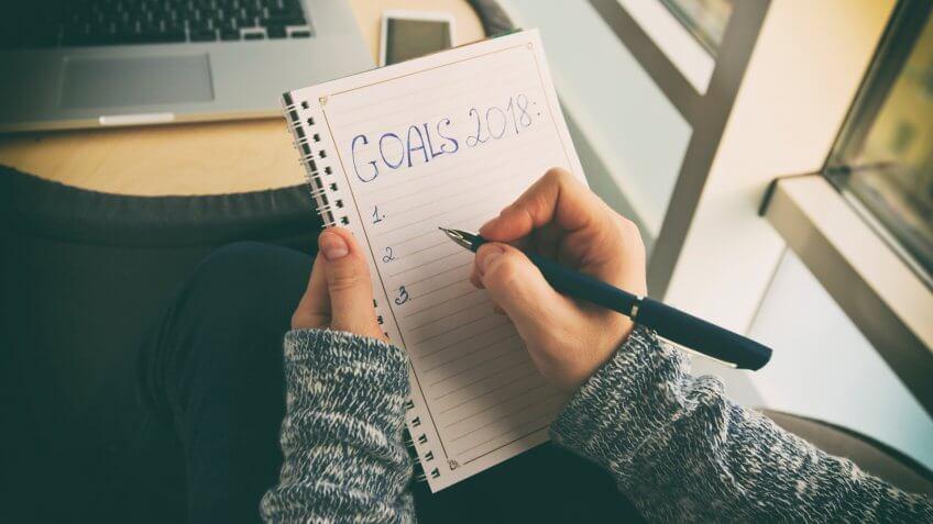 La mujer está escribiendo objetivos para 2018 año.
