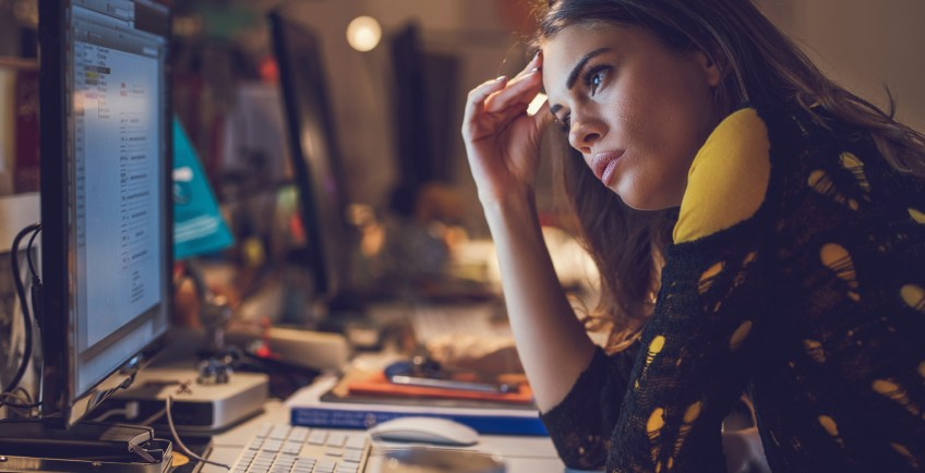 Young exhausted woman working late in the office.