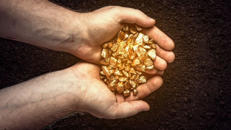 hands holding gold nuggets for investing