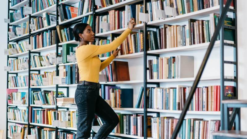 African american female librarian dressed in casual wear choosing literature book for exam preparation.