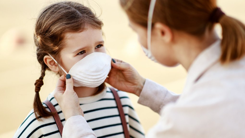 From above adult woman putting on medical mask of little girl while standing on city street during coronavirus pandemic.