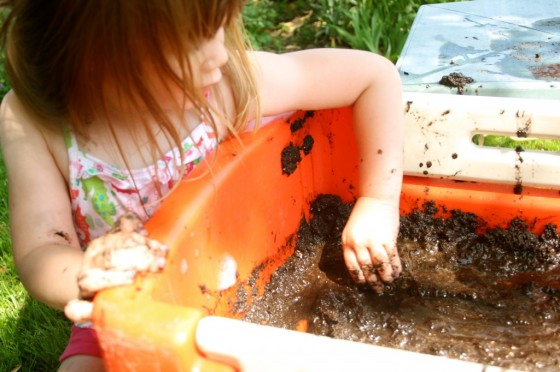 preschooler driving toy car in wagon filled with mud
