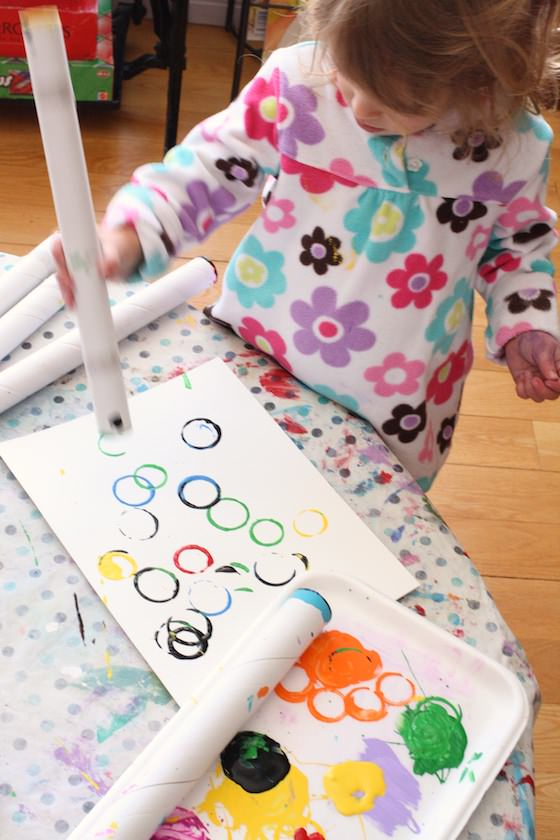 toddler making olympic rings craft with cardboard roll and paint