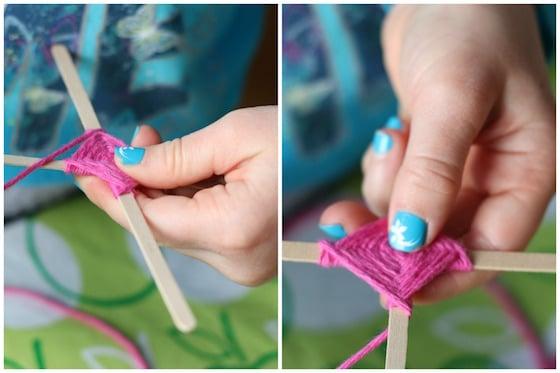 Wrapping pink yarn around 2 craft sticks