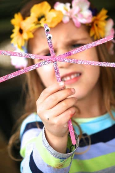 child holding dragonfly craft