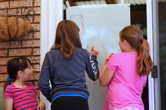 kids playing hangman on patio door with dry erase markers