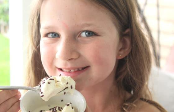 girl eating ice spoonful of homemade vanilla ice cream