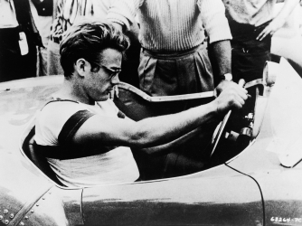 James Dean sits behind the wheel of a sports car in a still from 'The James Dean Story,' 1957. (Credit: Warner Bros./Getty Images)
