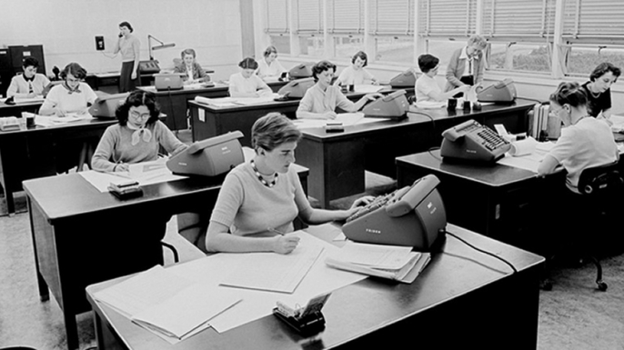 Macie Roberts' computing group circa 1955 (far right). Barbara Paulson is on the telephone (standing, back left). Helen Ling is at the second desk in the left row. (Credit: JPL)