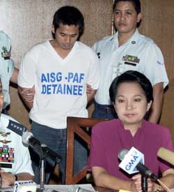 Abdulmukim Edris, standing with his head bowed in the back, and Philippine President Gloria Macapagal Arroyo, sitting in the front in purple.