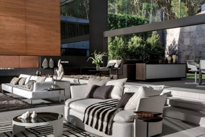 The interior design, by firm OKHA, uses modern lines, contemporary furniture, and plush area rugs to define smaller, more functional spaces within the vast open plan house, with a plethora of cushions and throws to add a sense of coziness despite the grand proportions.