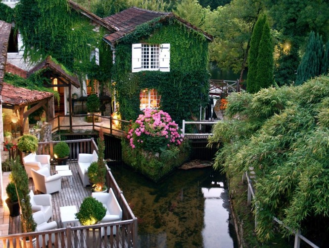 Le Moulin Du Roc Hotel in France is simply a living fairytale, adorned in rich greenery that cascades like an emerald waterfall around peeping window shutters and romantic balconies, just blissful!