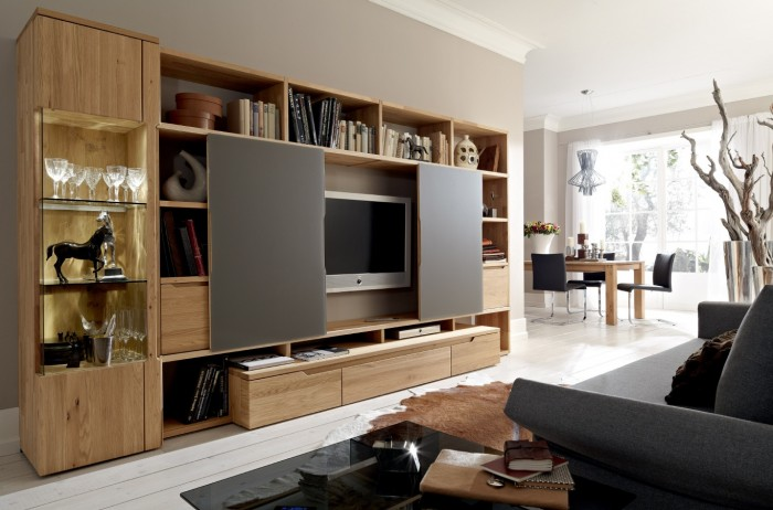 A rustic, richly grained wood finish highlights this large entertainment center which spans the wall in this modern living.