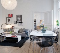The open living/dining space features unfinished wood floors, white walls and ceiling and filled with modern black, white and gray furnishings. The dining table is an open design which allows light to flow through the space as do the transparent plastic chairs. The coffee table also is open formed.
