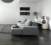 These dark stone tile floors create contrast with the bright white walls and gray furnishings. The design is clean and stylish.