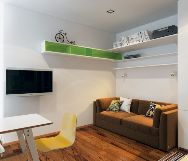 This first apartment is only 23 square meters (247 square feet) but makes beautiful, simple use of its small space. Here in the living room, we see how a small sofa sits perfectly into  a living room nook.