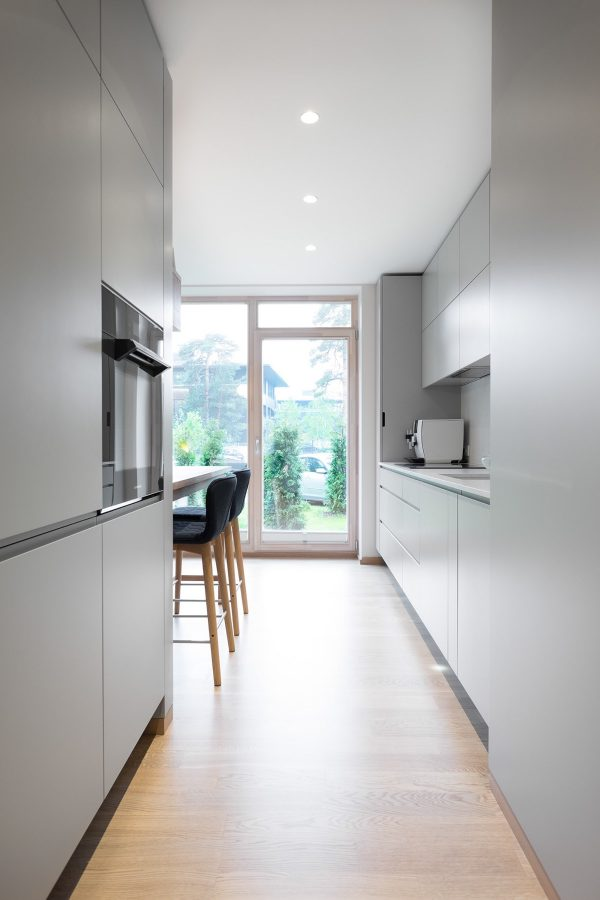 The Kitchen Is A Flat Fronted, Handle Free Design, With A Matching White  Corian Countertop. The Wall Cabinets Are Of The Same Plain White Design, ...