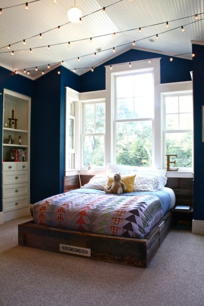 Cozy Bed with Huge Bedroom Window and String of Lights on Ceiling Teal Walls White Ceiling