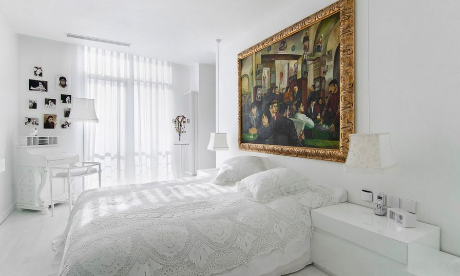 White bedroom with gold framed art above the bed