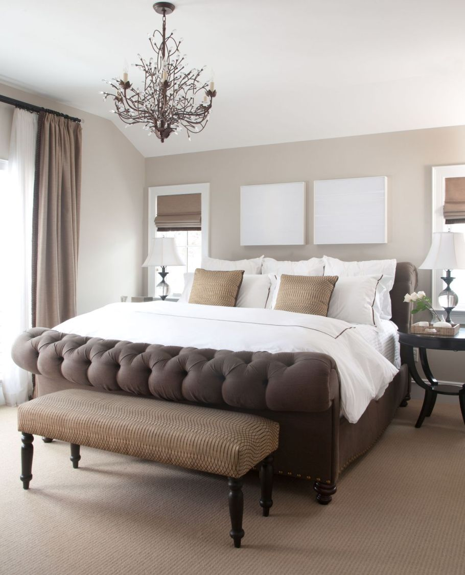 Tufted brown bed and chandelier over