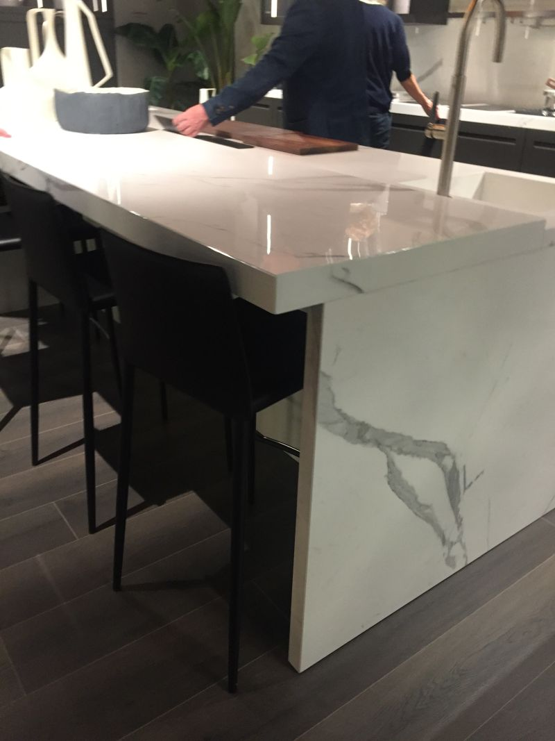 White marble kitchen island and stools under