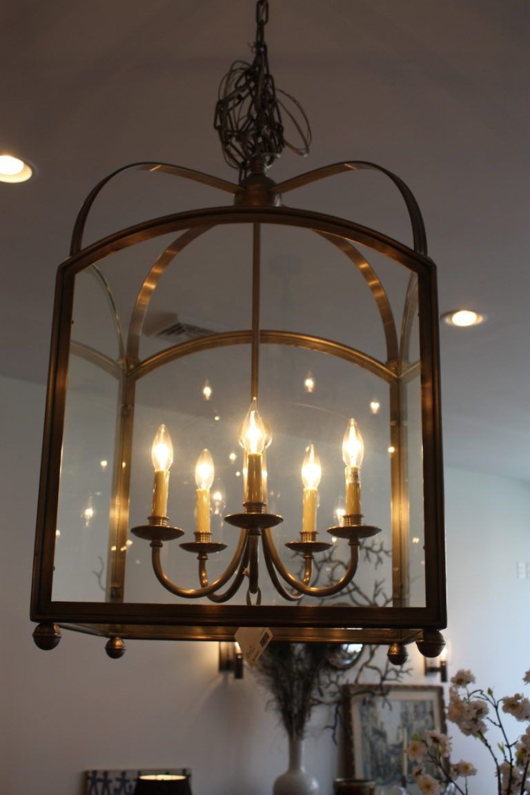 The Arch Top Lantern has five arms and features graceful curves, r in a brushed pewter finish. We love how it is a chandelier inside a glass enclosure.