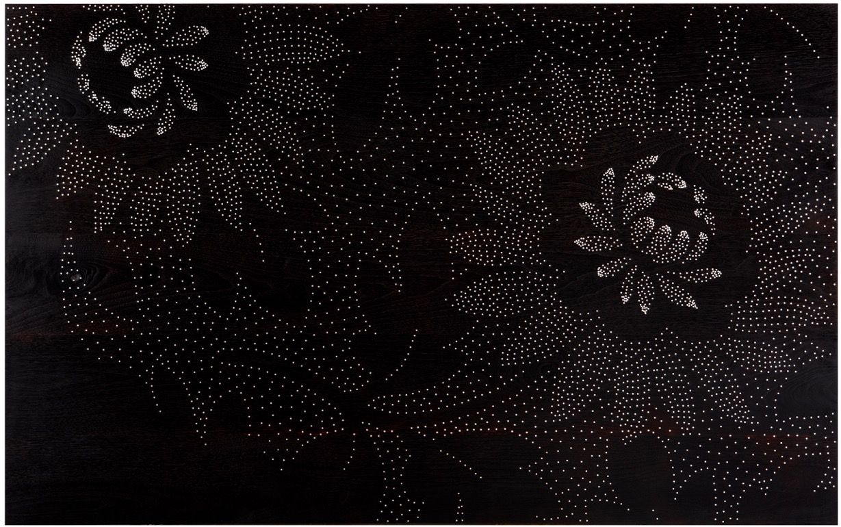 Detail of a floral motif on dark wedge wood.