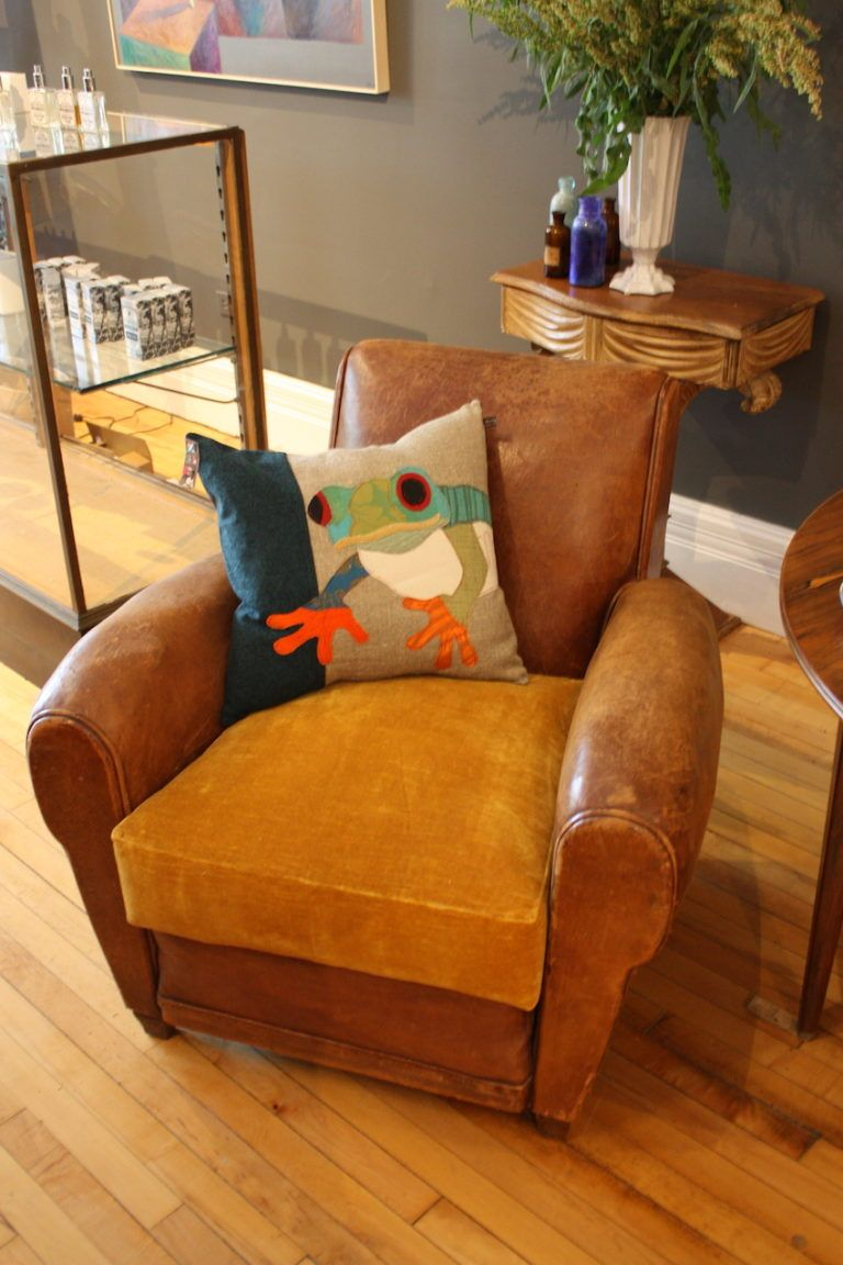 A vintage leather chair, paired with a whimsical frog pillow, is fun.