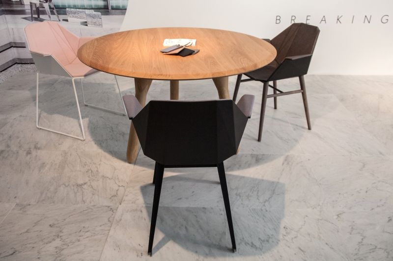 small mid century round dining table paired with geometric chairs