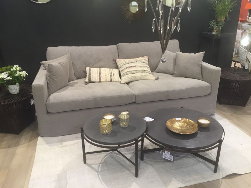 Black round coffee tables in front of a small grey couch