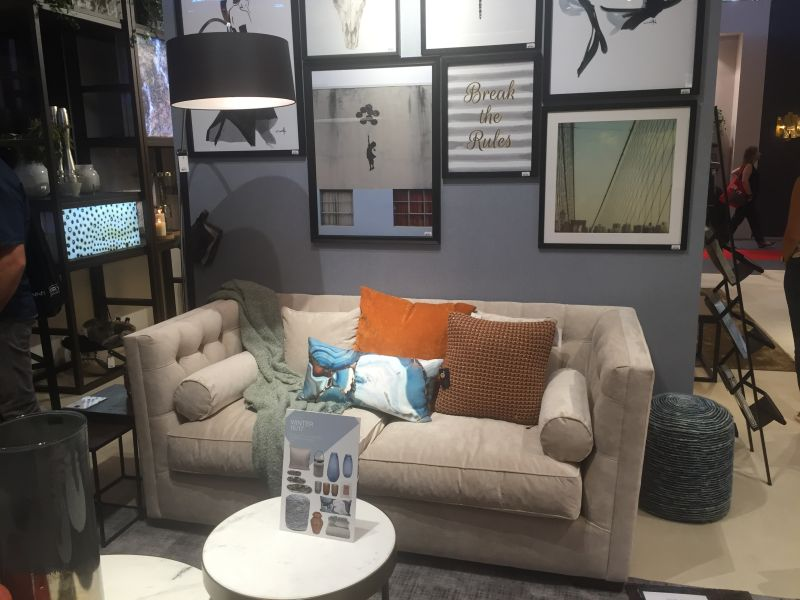 Small grey couch for a living with wall art frames