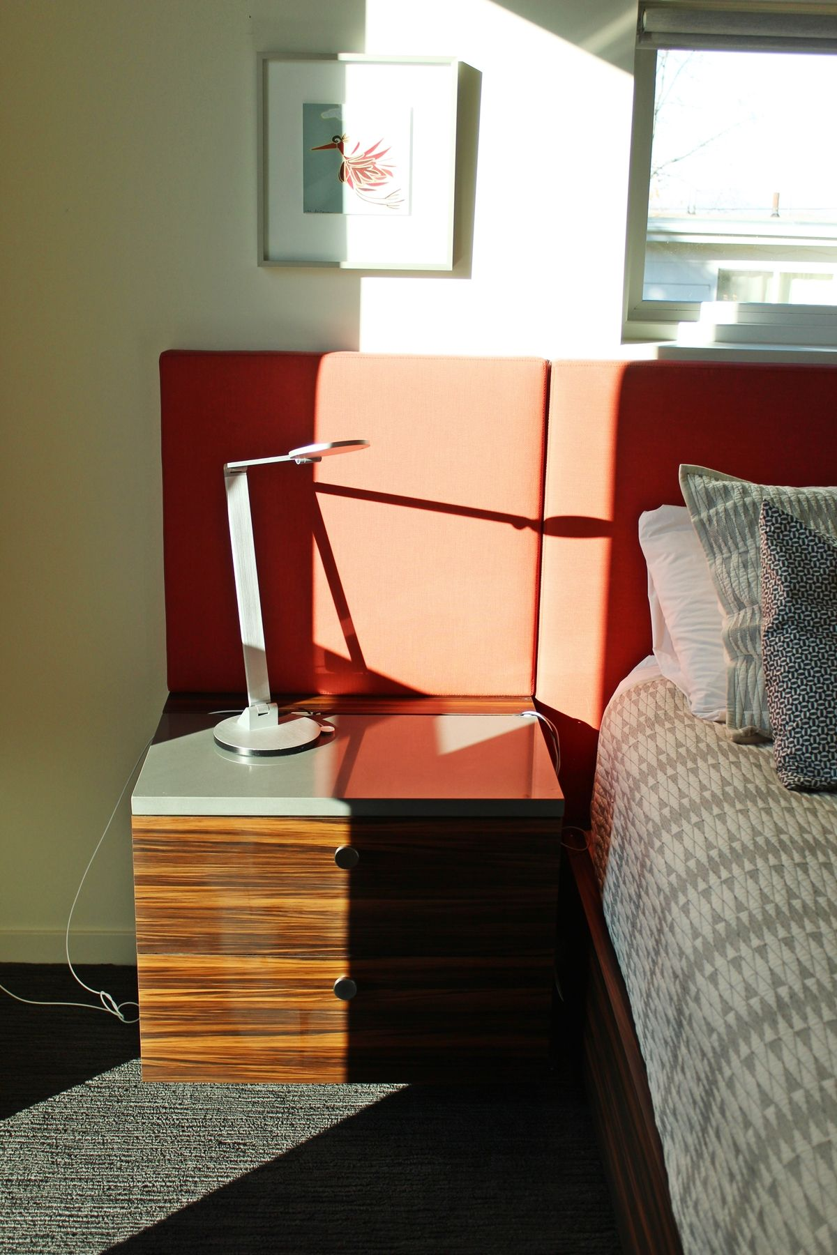 Red upholstered headboard extends to nighstand