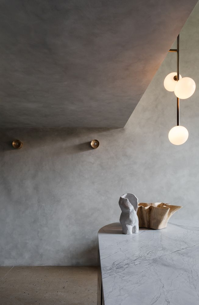Although it can look rather cold and austere, the concrete shell actually gives the apartment a cozy feel