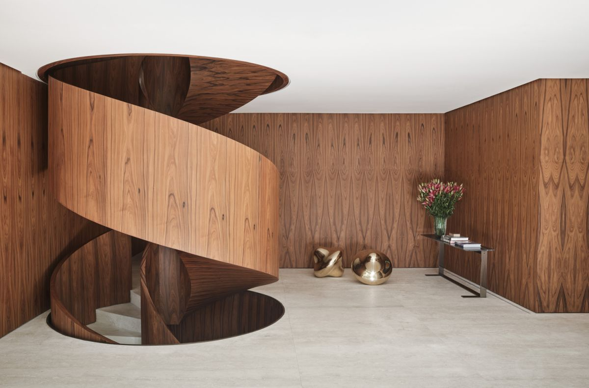 The use of wood extends beyond the spiral staircase and also encapsulates some of the walls