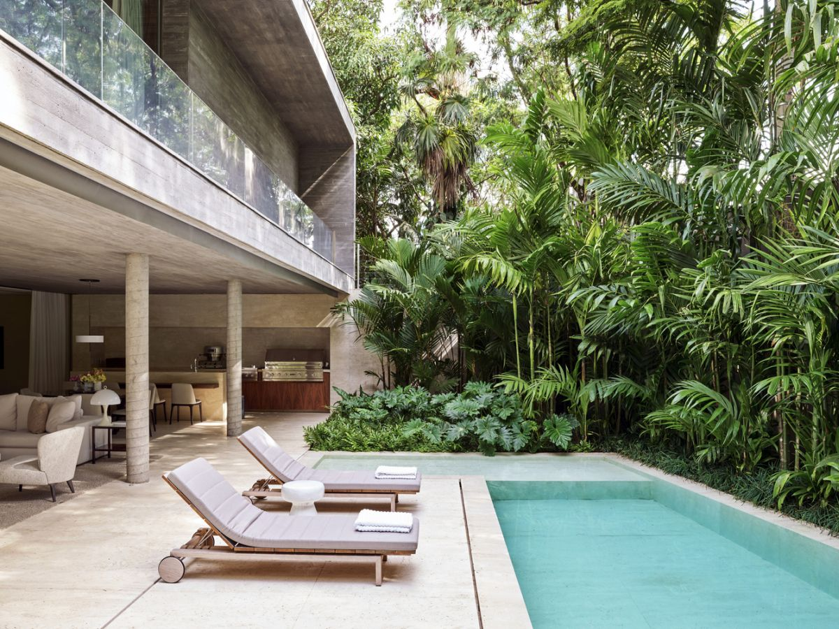 The living area extends outdoors and can become connected to the poolside deck