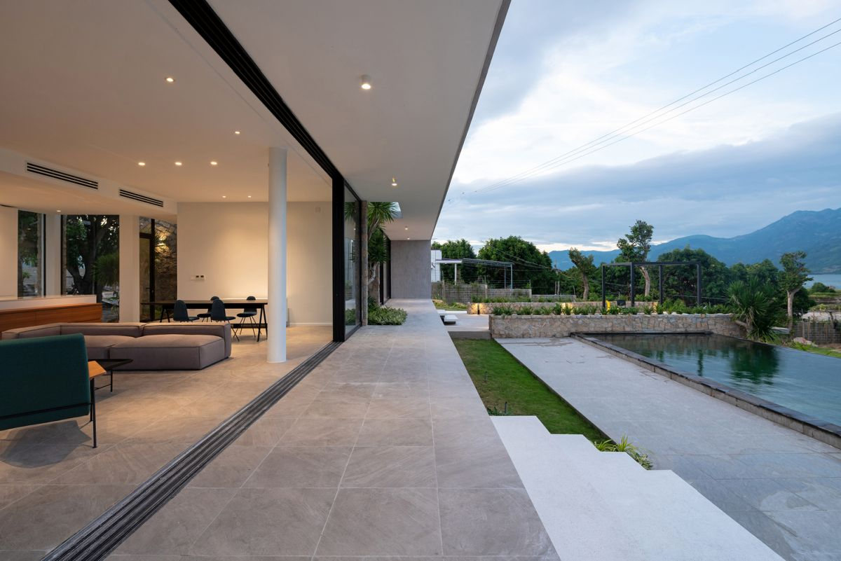 The indoor living areas transition out onto a terrace that's facing the swimming pool area