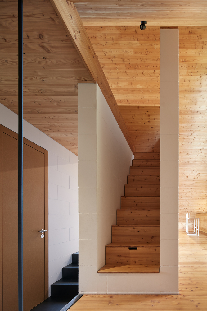 The staircase connecting the two floors is made of wood and framed in concrete